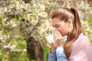 woman outside surrounded by flowering trees blowing her nose