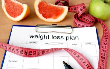 weight loss plan with raw fruit and measuring tape