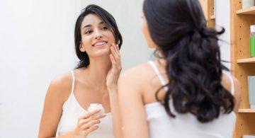 young woman in the bathroom admiring her reflection as she applies facial cream