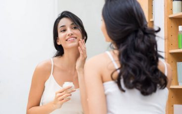 young woman in the bathroom admiring her reflection as she applies facial cream