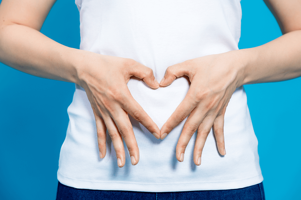 Woman making a heart with her hands over her stomach