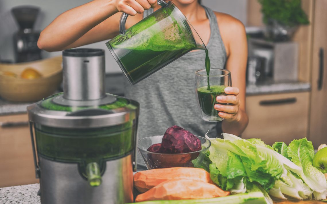 woman pouring homemade green juice with a juicer and vegetables on the counter