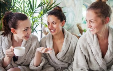 Three women chat while relaxing in robes at the spa