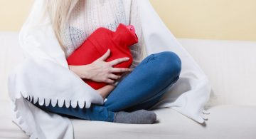 Woman holding a hot-water bottle to her stomach due to cramping