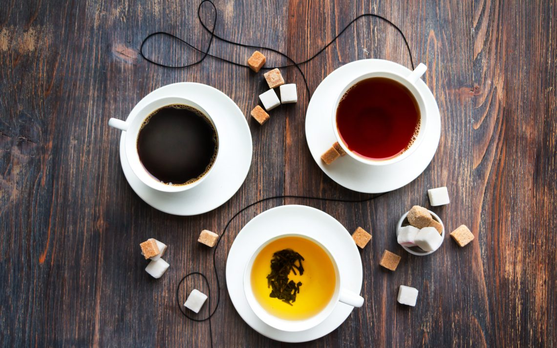 three cups of coffee and tea on wooden table