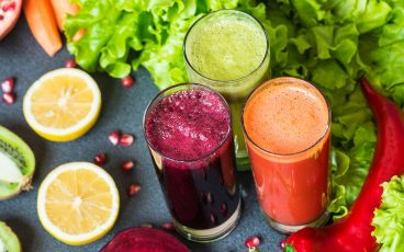 Three glasses of fresh juice surrounded by fruits and vegetables