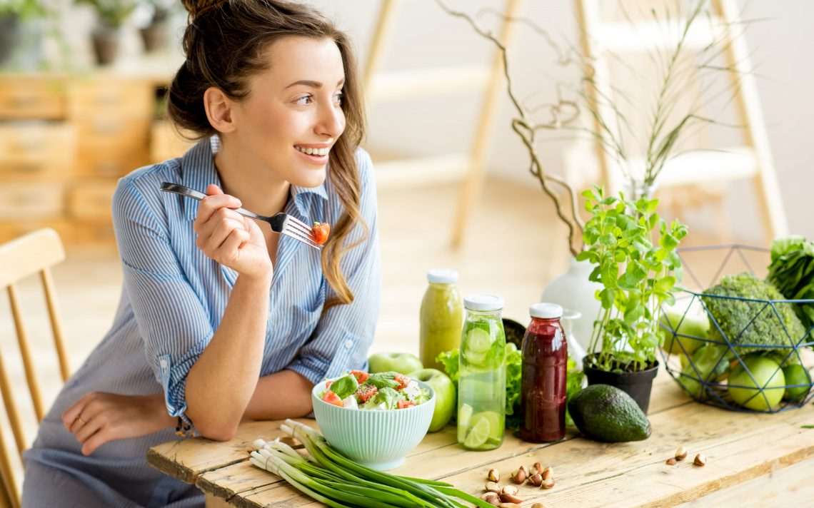 Happy woman eating a salad
