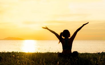 Silhouetted woman with hands in the air in front of an ocean sunset